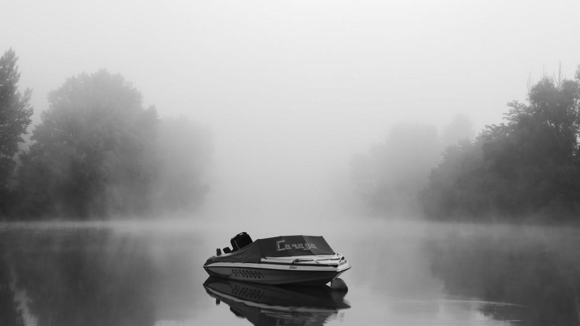 Un petit bateau sur le Tarn dans une ambiance très brumeuse du lever du jour; Image de Matthieu Dupont