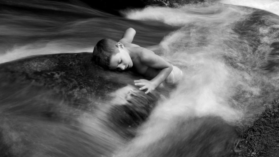 Un enfant allongé sur un rocher au milieu du courant d'un petit ruisseau ardéchois. Photographie en noir et blanc de Matthieu Dupont