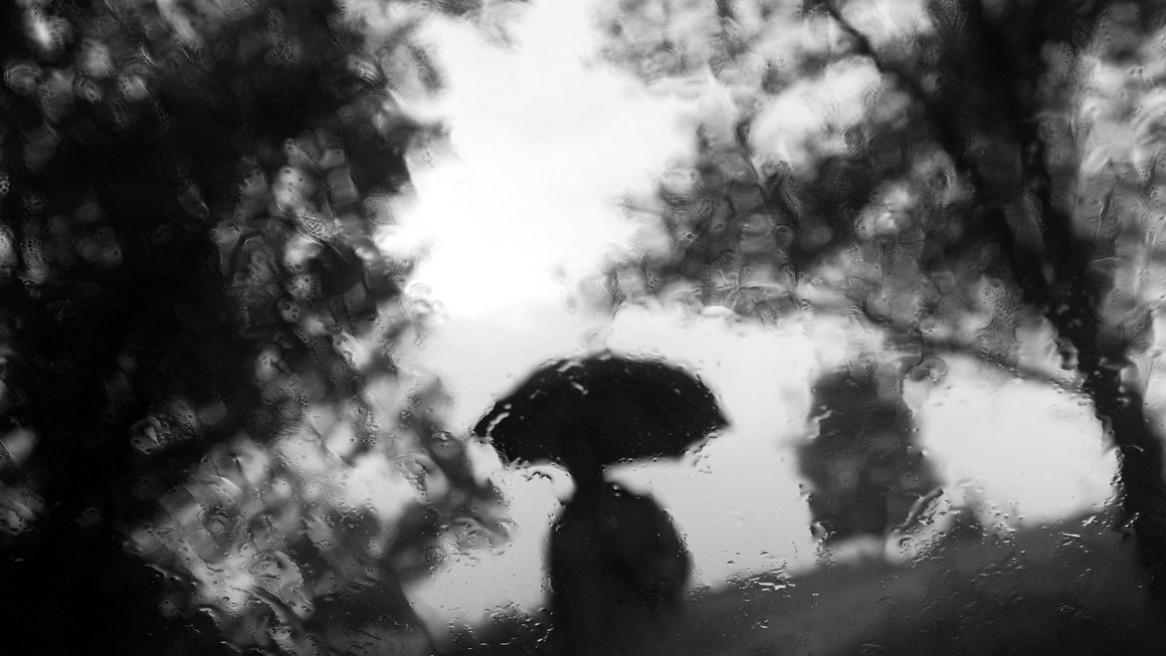vue depuis une fenêtre humide, une silhouette sous un parapluie s'approche. Photo Matthieu Dupont