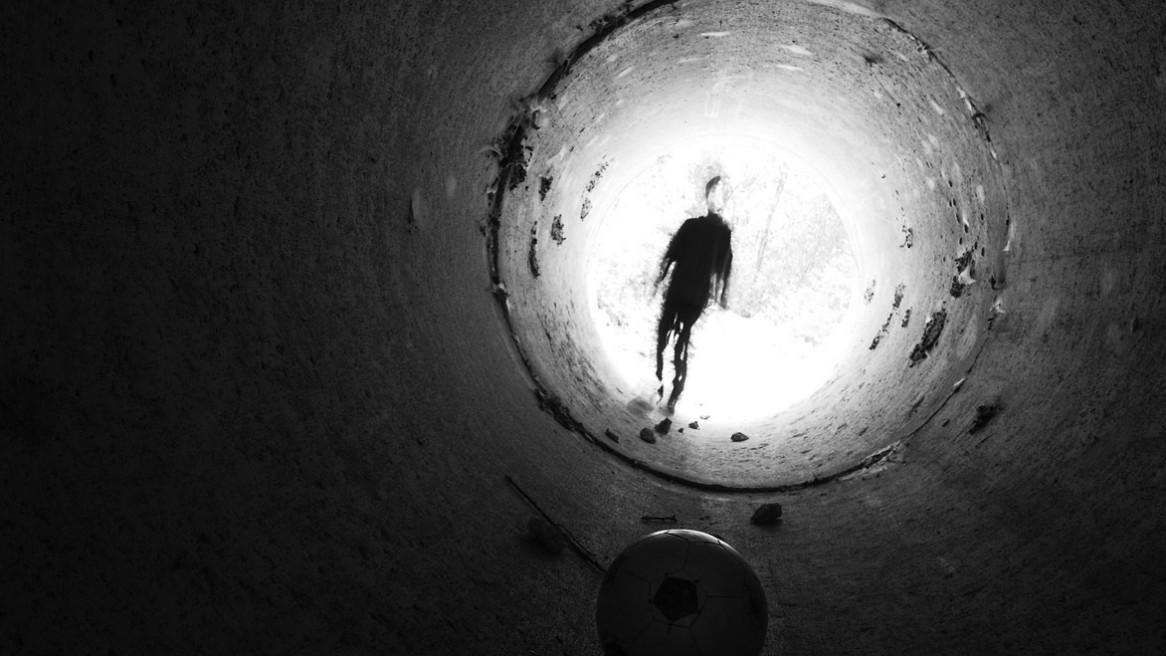 Un ballon posé dans un tunnel et un enfant à la silhouette étrange qui s'en approche.