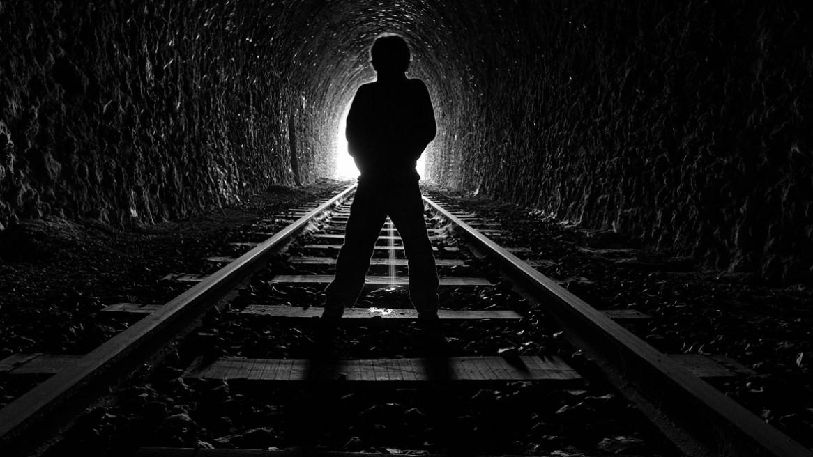 Un petit garçon urinant sur les rails d'une voie de chemin de fer désaffectée en Ardèche