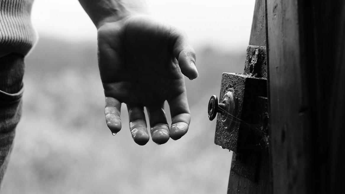Une main qui s'apprête à saisir la poignée d'une vieille porte. Une petite goutte d'eau sur le bout du doigt.