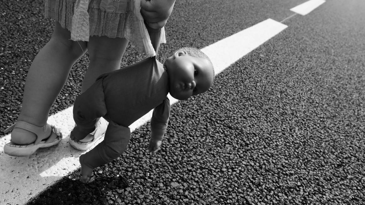 Une petite fille marche sur les bandes blanches d'une route, sa poupée à la main - Image noir et blanc de Matthieu Dupont