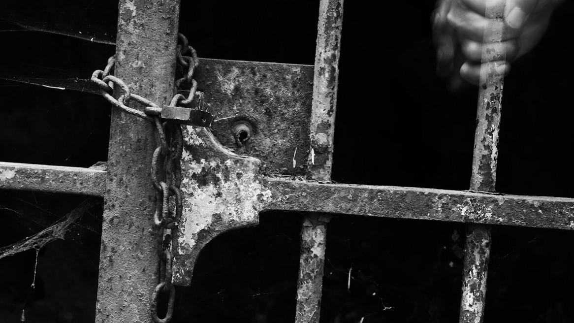 Une main serrant le barreau d'une grille - Photo noir et blanc de Matthieu Dupont
