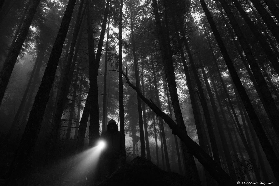 Une forêt sombre, une légère brume, une silhouette, une lampe torche... Une scène pesante, photographiée par Matthieu Dupont
