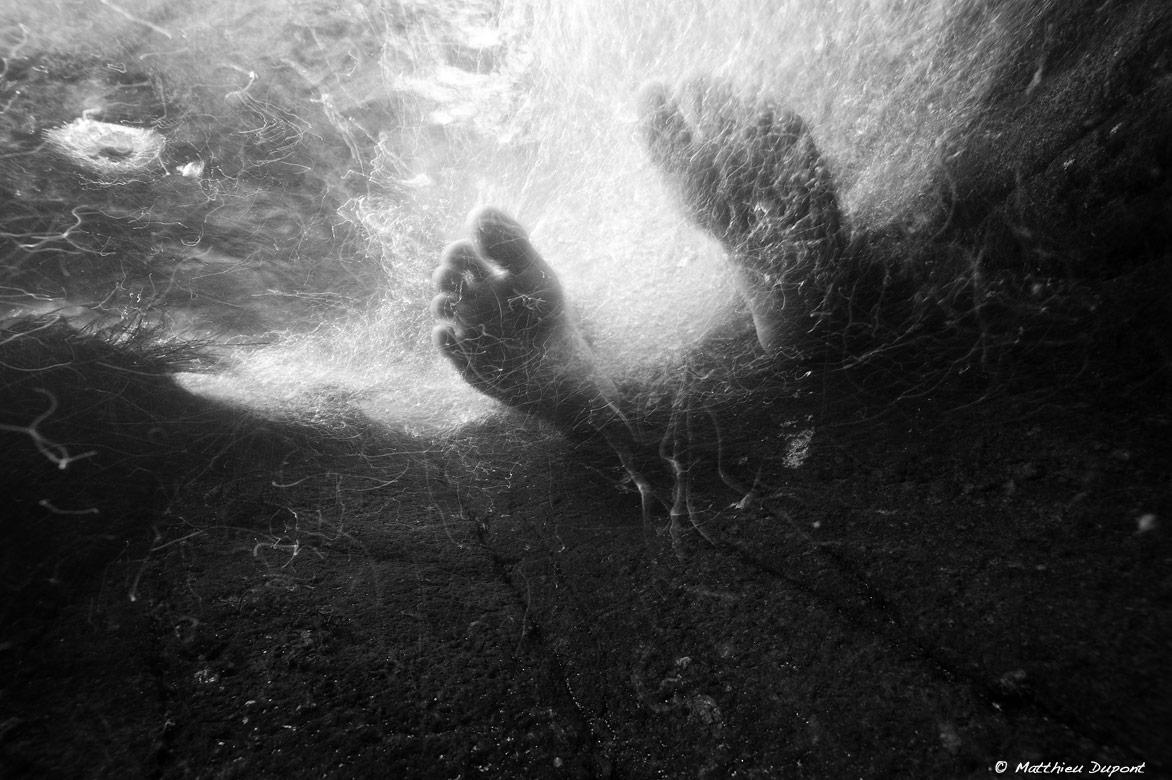 Photo sous l'eau en noir et blanc de pieds dans le courant, par Matthieu Dupont