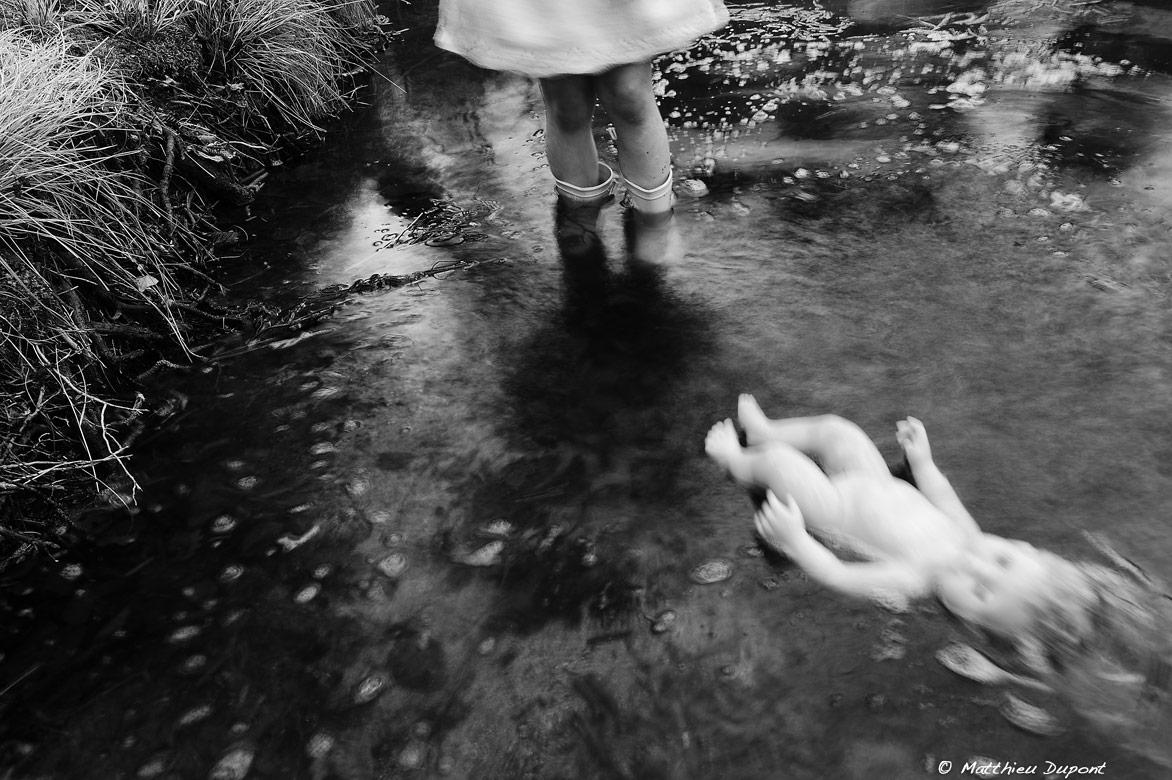 Une petite fille laisse partir sa poupée dans le courant. Photo Matthieu Dupont